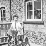 Peter Woods on his tricycle in front of the 'Towler's Court' cottage c. 1940-1.