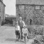 Image of the garden of the Woodrow house, looking towards Market Hill (beyond the double gate). Peter Woods, his sister and grandfather.